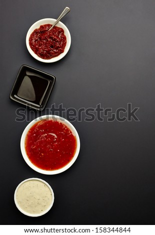 various sauces on black background - stock photo