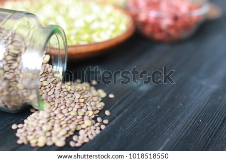 various seeds of legumes, sprouts of chickpeas and beans on a dark wooden kitchen table
