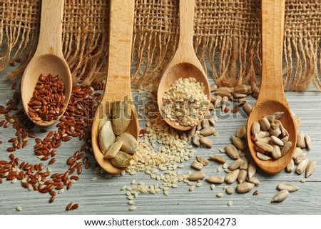 Various seeds on blue wooden background, closeup
