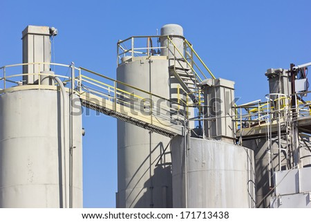 Various sizes in silos are connected and access by stairs and an elevated walkway.   - stock photo