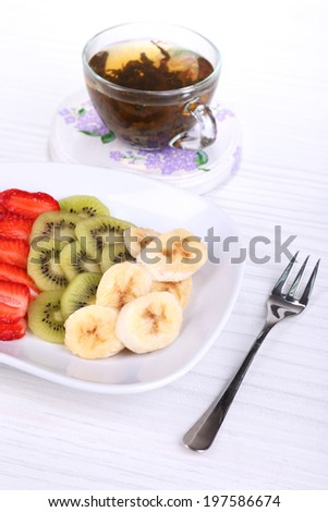 Various sliced fruits on plate on table close-up