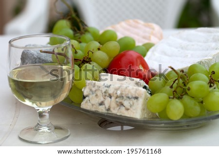 Various sorts of cheese, grapes and glass of the white wine - stock photo