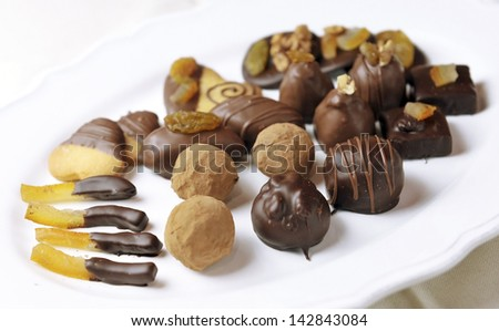 Various sorts of luxury confectionary chocolate on white plate - stock photo