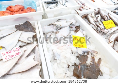 Various species of fresh fish at a fish market displayed in plastic trays or tubs with ice and price tags in a sea fisheries, seafood, and retail concept - stock photo