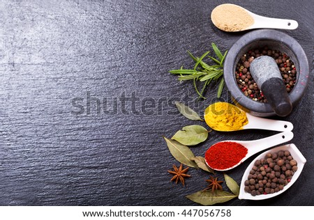 various spices and herbs on dark background - stock photo