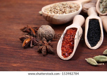 Various spices and herbs on wooden table - stock photo