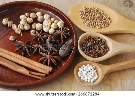 various spices for chinese food boiled decorate on ladle round tray and wooden background - stock photo