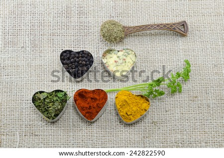 Various spices in heart shaped containers and a spoon full of oregano on a tablecloth - stock photo