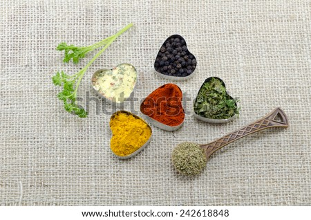 Various spices in heart shaped containers and a spoon of oregano - stock photo