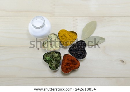 Various spices in heart shaped containers with salt on a table - stock photo