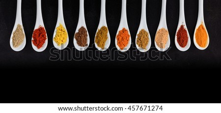 Various spices in porcelain spoons, black background - stock photo