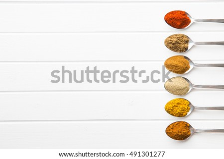 Various spices in spoons on white table. Top view.