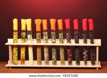 Various spices in tubes on wooden table on red background