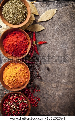 Various spices in wooden bowls on stone surface