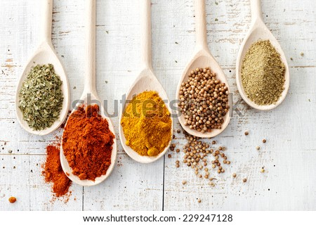 various spices in wooden spoons on old white wooden table - stock photo