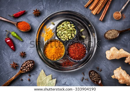 Various Spices like turmeric, cardamom, chili, bayberry, bay leaf, paprika, ginger, cinnamon, cumin, star anise and clove on grunge background  - stock photo
