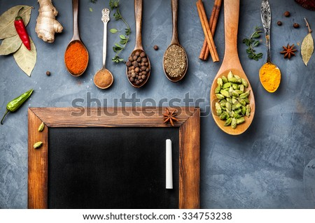 Various Spices like turmeric, cardamom, chili, ginger, star anise and cinnamon near blackboard on grunge background. Free space for your text  - stock photo