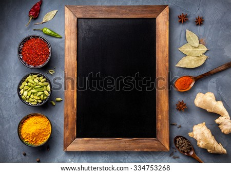 Various Spices like turmeric, cardamom, chili, paprika, ginger, star anise and clove near blackboard on grunge background. Free space for your text