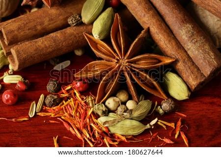 various spices (nutmeg, cinnamon, star anise, saffron, pepper, cardamom, fennel) - stock photo