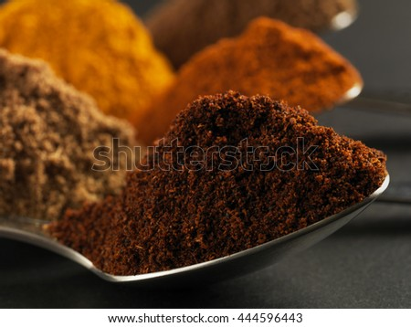 Various spices on spoons on black background
