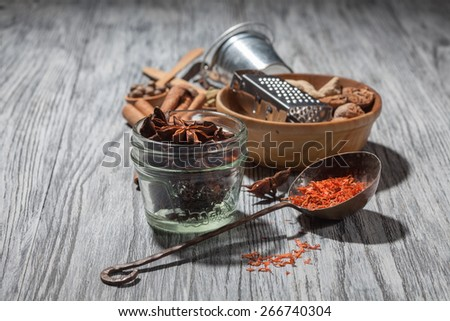 Various spices on wooden background - anise, cardamon, cinnamon, ginger, clove, nutmeg, papper and saffron - stock photo