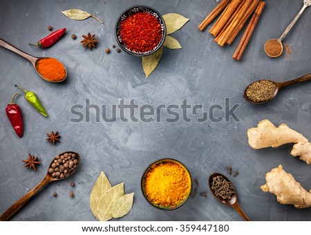 Various Spices powder turmeric, chili, bayberry, bay leaf, ginger, cinnamon, cumin, star anise on grey stone background with space for your text, shot from aerial view close-up - stock photo
