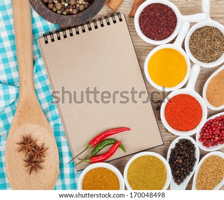 Various spices selection and notepad for copy space on wooden table - stock photo