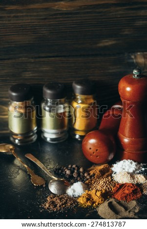 Various spices with spoons on a black background