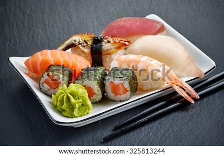 various sushi on black table - stock photo