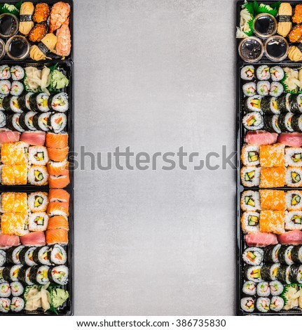 Various Sushi sets : rolls , nigiri , maki and uramaki in black packaging tray on gray  stone background, top view, frame.  Japanese and Asian food. - stock photo