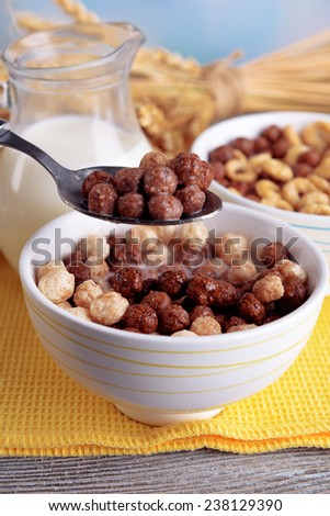 Various sweet cereals in ceramic bowl, fruits and jug with milk on napkin, on wooden table, on light background - stock photo