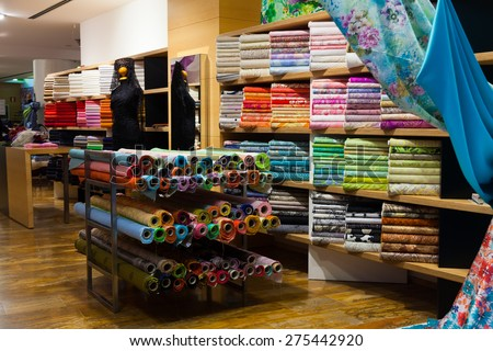 various textiles for sale in fabric shop - stock photo