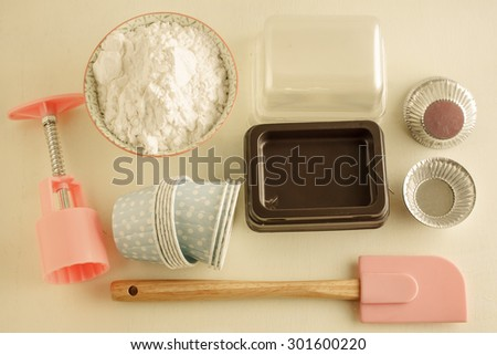 Various tins and paper cases for tartlets and muffins. image vintage tone. - stock photo