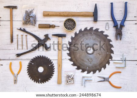 Various tools and nails on a wooden background - stock photo