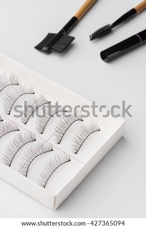 Various tools for applying make-up for eyes. Accurate rows of false eyelashes in the paper box. Cosmetical instruments for brushing and taking care of lashes and brows. - stock photo