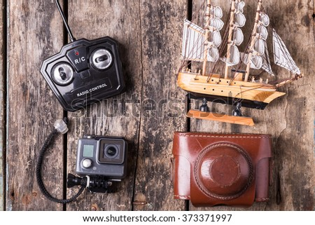 Various toys for different ages. Action camera, old film camera, remote control and model of sailing ship on wooden background.