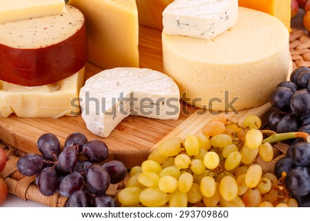 Various type of cheese and grapes on wooden board closeup picture. - stock photo