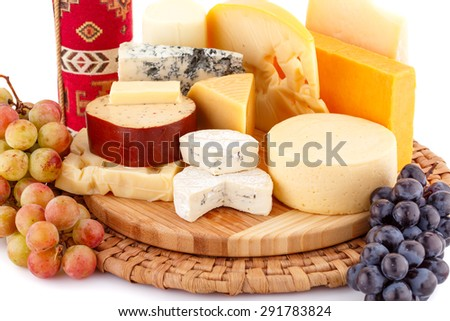 Various type of cheese,wine and grapes on wooden board closeup picture. - stock photo