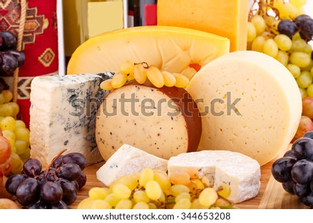 Various type of cheese, wines and grapes on wooden board closeup picture. - stock photo
