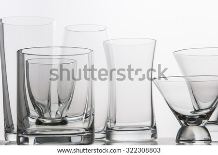 various type of glasses on a mirrored desk