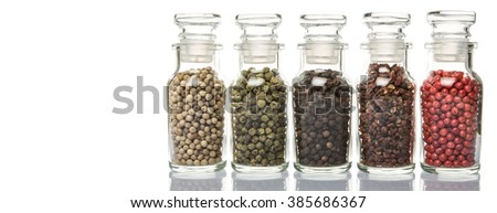 Various type of peppercorns in glass vial over white background