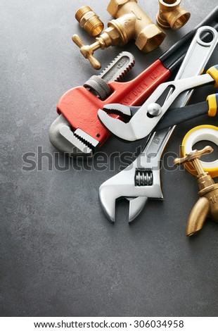 various type of plumbing tools on grey tile - stock photo