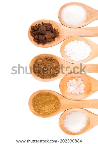 Various type of sugar on wooden spoons over white background - stock photo