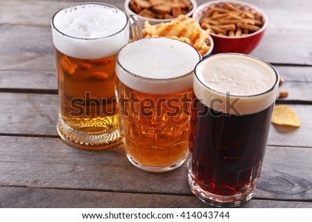 Various types of beer and snacks on wooden table - stock photo