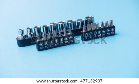 Various types of bits or heads for hex screwdriver or hexagon screwdriver bolts fasteners. Isolated on blue background. Slightly de-focused and close-up shot. Copy space.