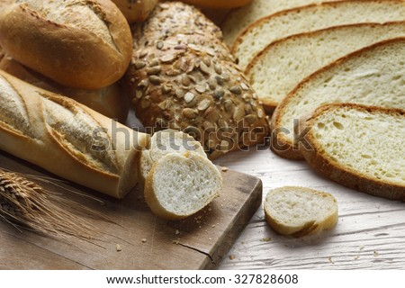 Various types of bread on a white wooden table with wheat and bread slices - stock photo