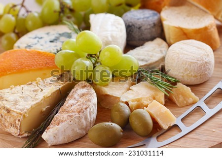 Various types of cheese and knife on wooden board - stock photo