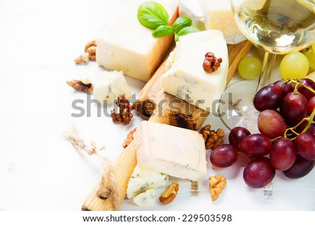Various types of cheese, cheese board with grapes and wine