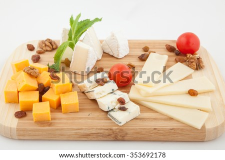 Various types of cheese composition on wooden board - stock photo