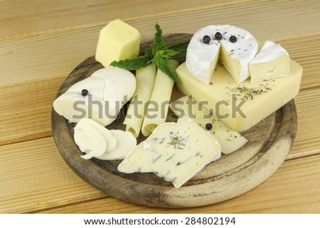 Various types of cheese on a cutting board, made from cow's milk. - stock photo